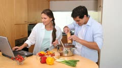 Couple using a laptop are cooking together Stock Footage