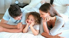Child lying between his two parents Stock Footage