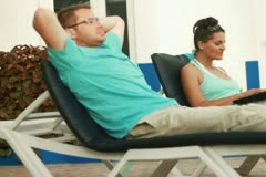Couple with laptop relaxing on sunbeds, dolly shot Stock Footage