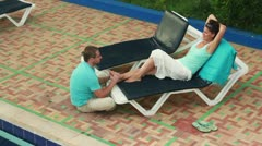 Young happy man giving massage woman by the pool - stock footage