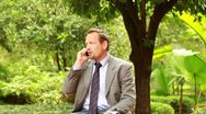Businessman with cellphone in the park, steadicam shot Stock Footage