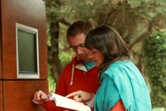 Couple in the park typing on touchscreen, steadicam shot Stock Footage