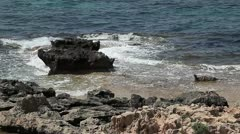 The dark waters of the Mediterranean sea, hit a coral beach. - stock footage
