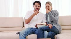 Couple eating popcorn while watching a movie Stock Footage