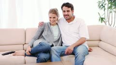 Smiling couple sitting on the couch while watching the television - stock footage
