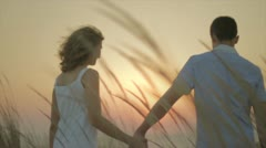 Young couple walking in sunset Stock Footage