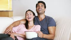 Laughing couple watching the television Stock Footage