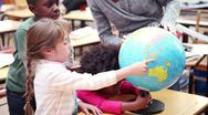 Teacher showing a globe to her pupils Stock Footage