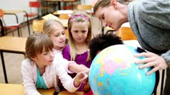 Pupils pointing at a globe - stock footage