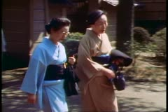 Two Japanese women in traditional kimonos pass at Kamakura in Japan, - stock footage