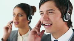 Smiling call centre agents using headsets - stock footage