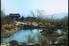 A scene of South Korea near Pusan with a lake and temple backlit Stock Footage