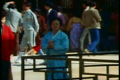 Buddha Land Temple, women walks through courtyard, bows, in traditional dress Stock Footage
