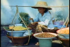 Stock Video Footage of Bangkok street market, produce seller wearing traditional lampshade like hat