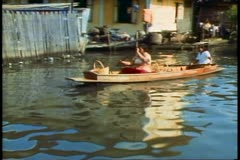 The Klongs of Bangkok, the canals and waterways, two women pass - stock footage