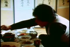 Stock Video Footage of Two men have a traditional Korean lunch at low table using chopsticks,