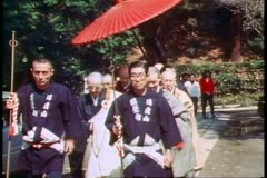 Shinto priests with large umbrella pass in a ceremony, Kamakura in Japan, - stock footage