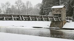 Snow Covered Rustic Foot Bridge Over Icy River Stock Footage