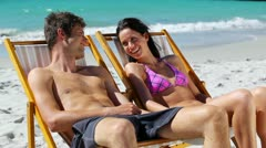 Relaxed couple sitting on deck chairs Stock Footage