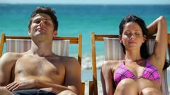 Couple resting on deck chairs Stock Footage