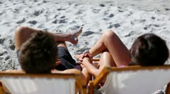 Happy couple sitting on deck chairs Stock Footage