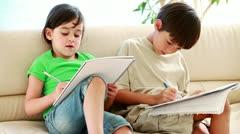 Happy siblings doing their homework - stock footage