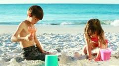 Siblings building sand castles Stock Footage