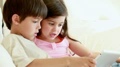 Smiling children holding a tablet computer - stock footage