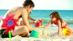 Children building sand castles with their father Stock Footage