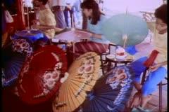 Young women painting parasols in Bangkok Stock Footage