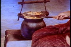 Old woman spinning silk in Bangkok, silk worms in a simmering pot - stock footage