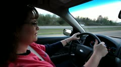 Woman driving down interstate highway with buses and trucks going by Stock Footage
