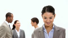 Smiling businesswoman with co-workers behind her - stock footage