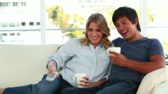 Smiling couple relaxing while watching the television Stock Footage