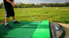 Closeup of young boy hitting golf ball at driving range Stock Footage