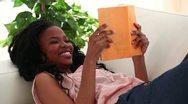 Happy woman reading a novel Stock Footage