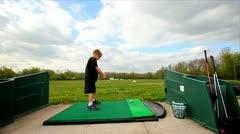 Cool wide angle shot of boy hitting golf balls Stock Footage