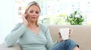 Woman on the phone holding a mug Stock Footage