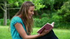 Smiling young woman reading a novel Stock Footage