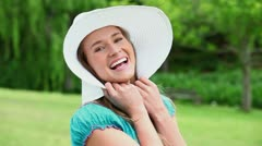 Cheerful young woman holding her hat brim - stock footage