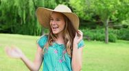 Happy woman holding her straw hat Stock Footage