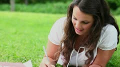 Brunette woman seriously writing Stock Footage