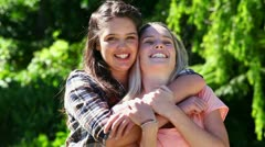 Happy woman placing her arms around her friend Stock Footage