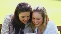 Smiling friends looking at a digital camera Stock Footage