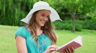 Happy young woman reading a fascinating book Stock Footage