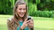 Smiling young woman typing on her cellphone Stock Footage