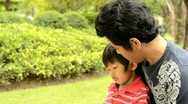 Stock Video Footage of Asian Father and Son Reading Together in a Park