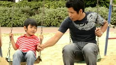 Father and Son Playing on a Swing Together - stock footage
