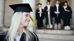 Happy friends standing behind a blonde student Stock Footage