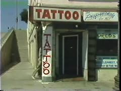 Two Men Walk Into Tattoo Parlor Stock Footage